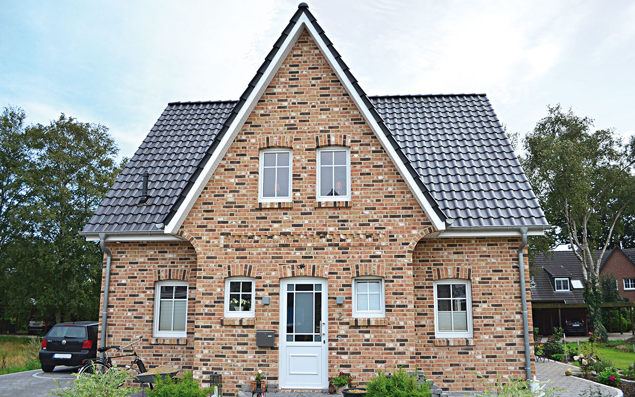 Friesenhaus mit Einfahrt und schwarzem Dach