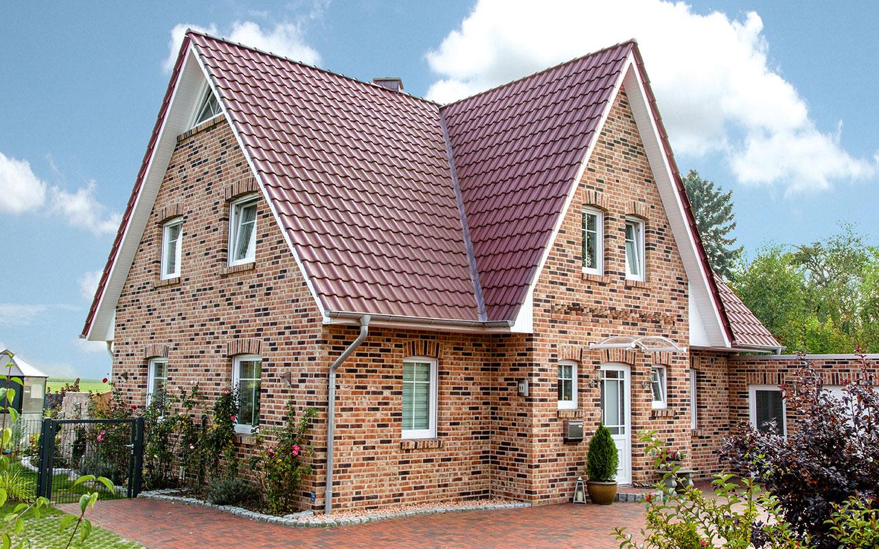 Friesenhaus mit Einfahrt und rotem Dach