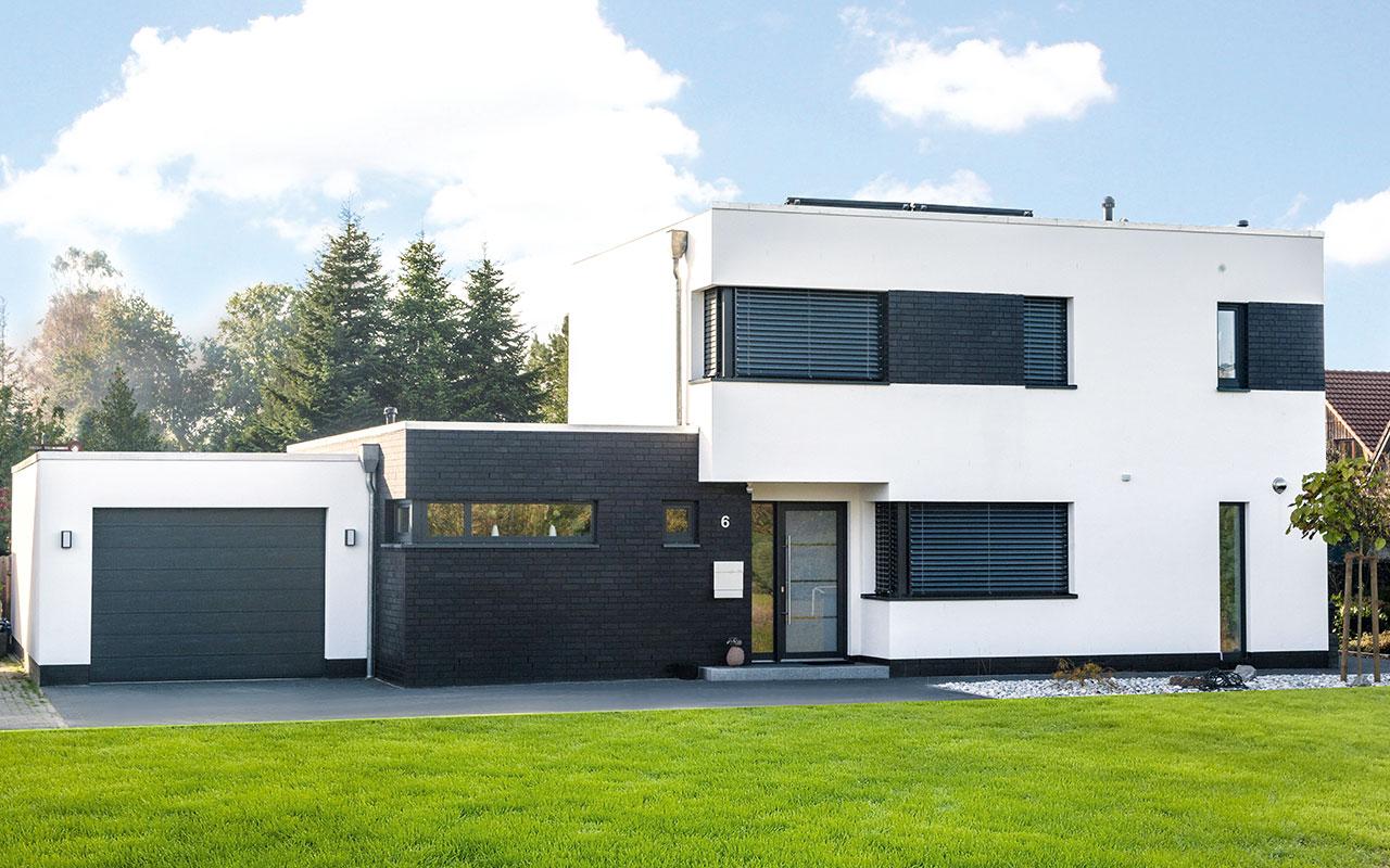 Weißes Flachdachhaus mit Garten und Garage