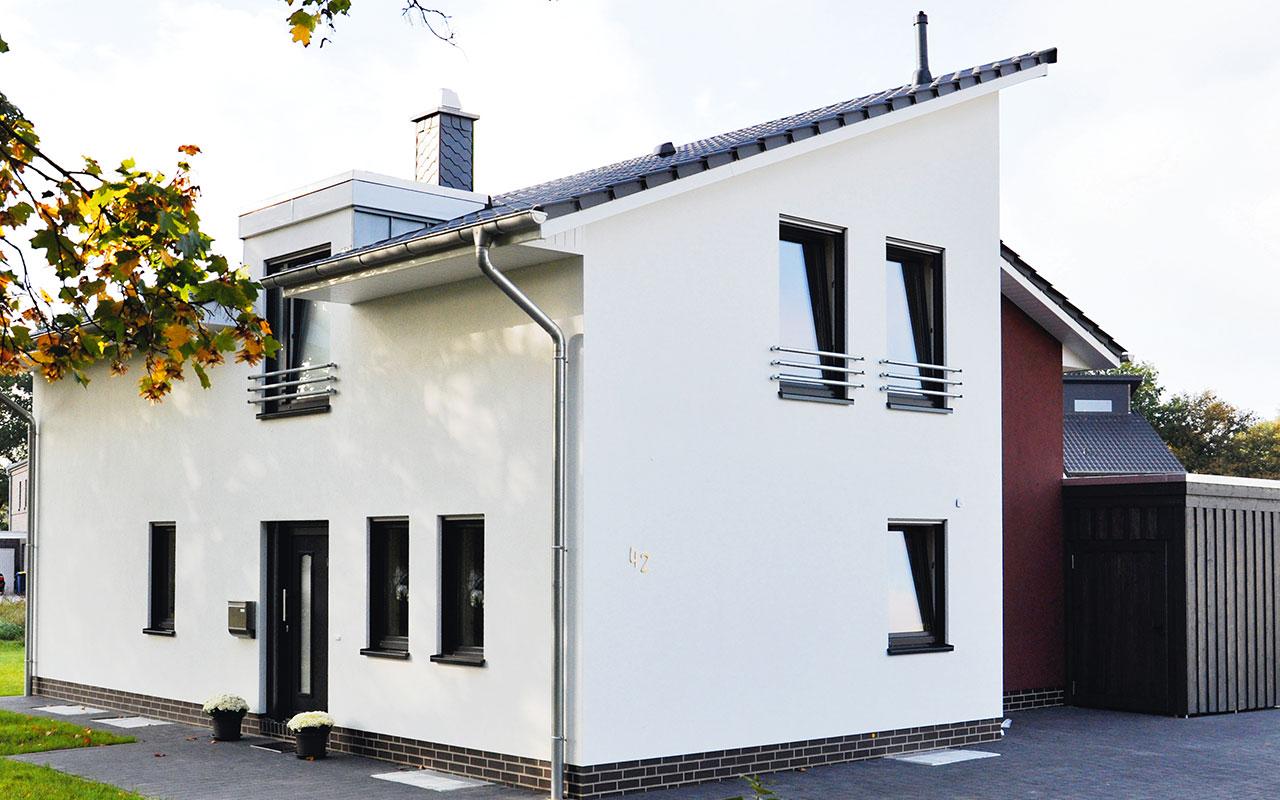 Weißes Pultdachhaus mit schwarzem Dach