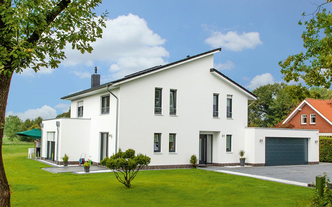 Weißes Pultdachhaus mit Garage und Garten