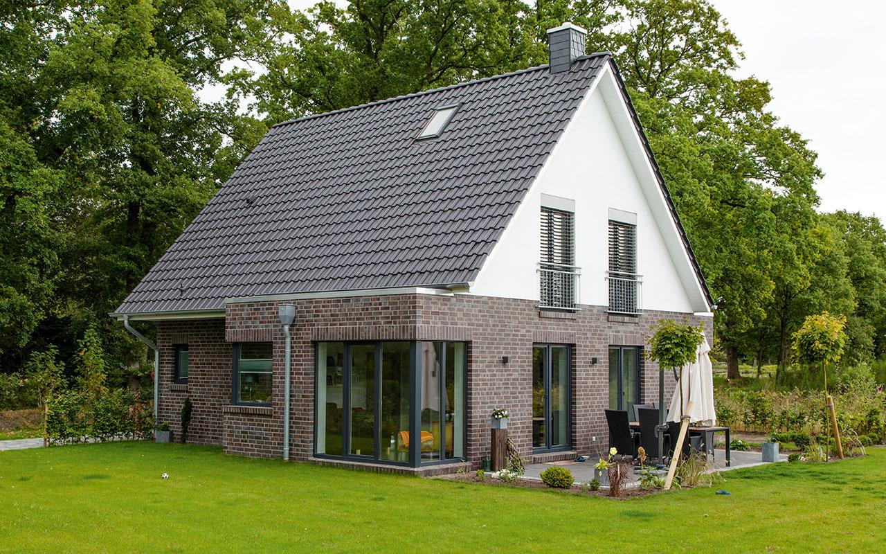 Satteldachhaus mit Fassadenmix und großen Fenstern