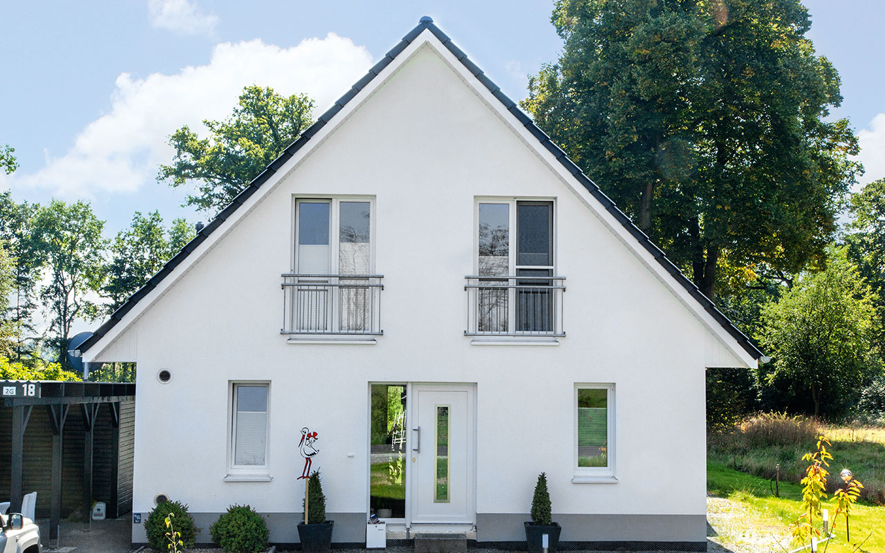 Weißes Satteldachhaus mit Carport und Garten