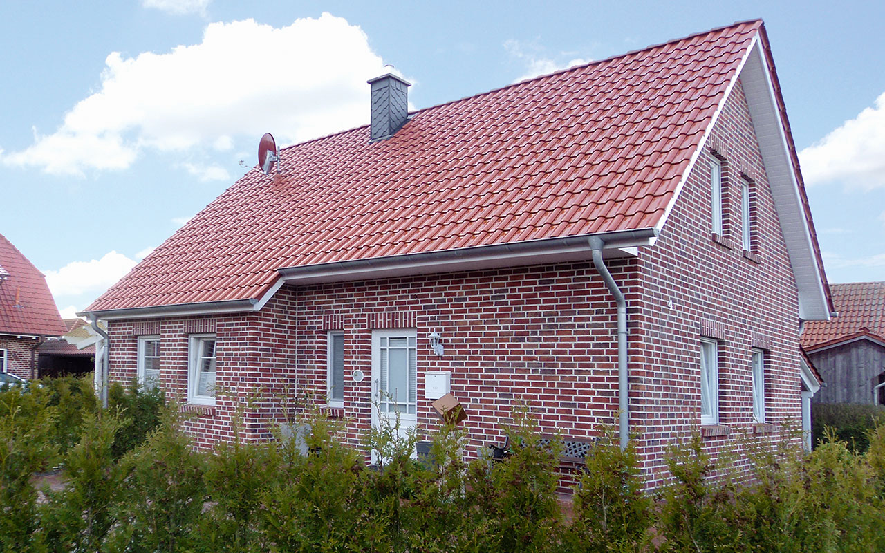 Satteldachhaus mit roten Klinkern und rotem Dach