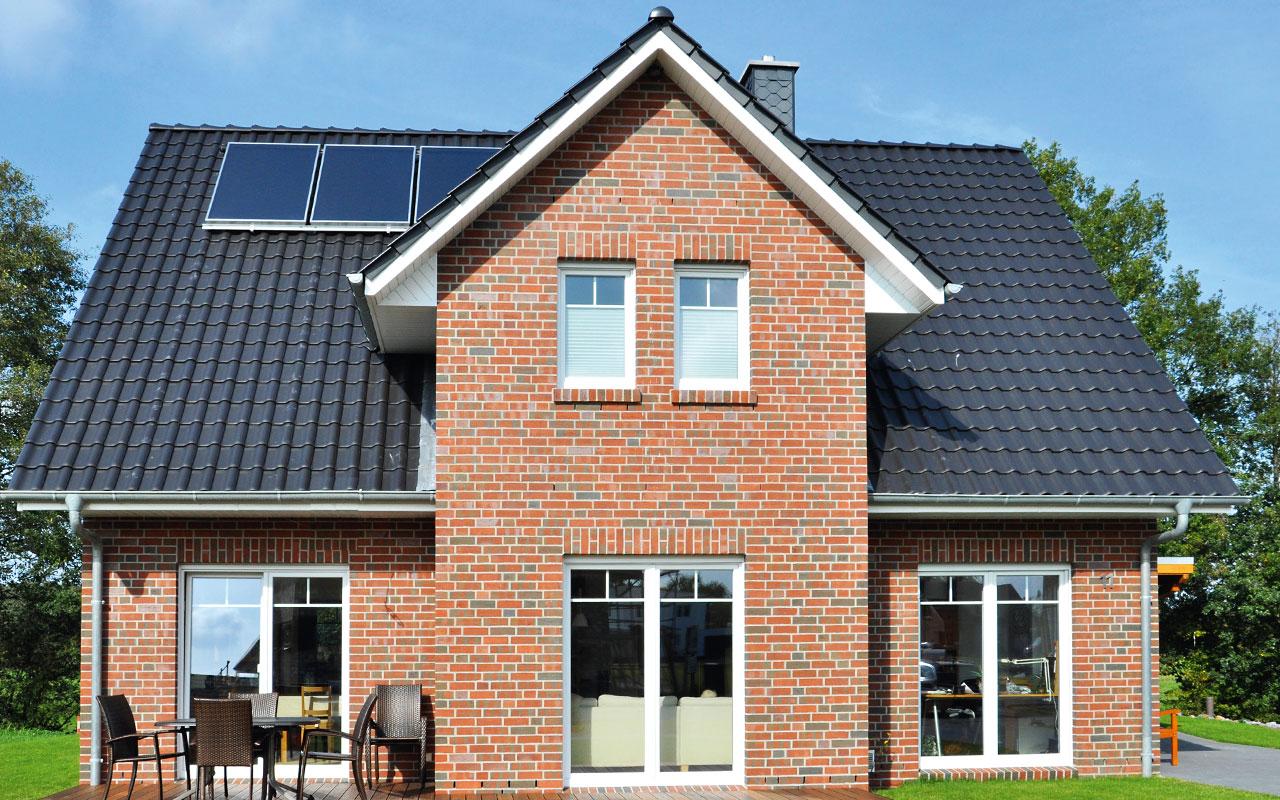 Zweifamilienhaus mit großen Fenstern und dunklem Dach