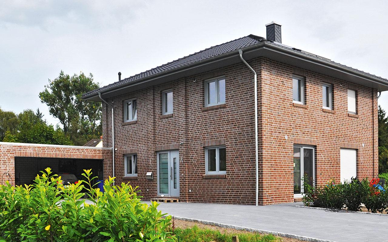 Zweifamilienhaus mit roten Klinkern und schwarzem Dach